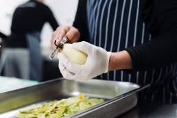 collective-hospitality-peeling-a-pear-in-the-kitchen
